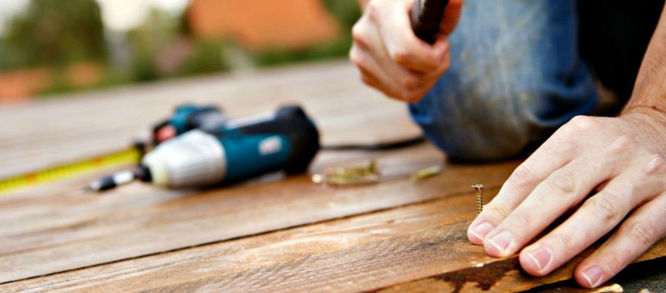 a professional from KCNP fixes a deck with a screw and a hammer