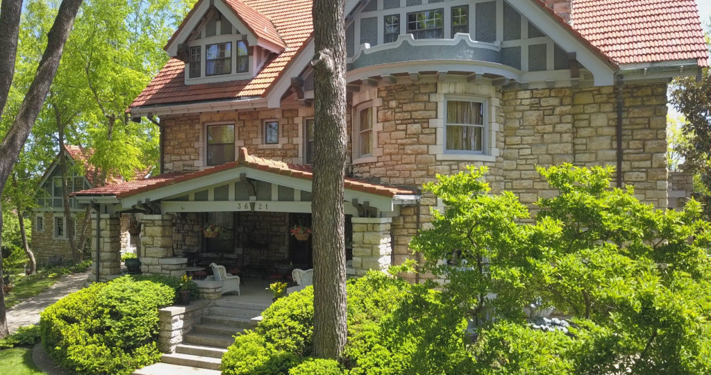 Two story stone home with exterior painting services.