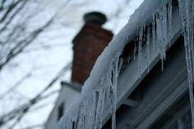 a gutter is filled with ice prior to being checked off of a home repair list in Kansas City